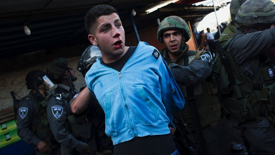 """Israeli security forces detain a Palestinian man during clashes that erupted during a rally marking Nakba Day in Jerusalem, Wednesday, May 15, 2013. Palestinians annually mark the """"nakba,"""" or """"catastrophe"""" — the term they use to describe their defeat and displacement in the war that followed Israel's founding in 1948. (AP Photo/Bernat Armangue)"""
