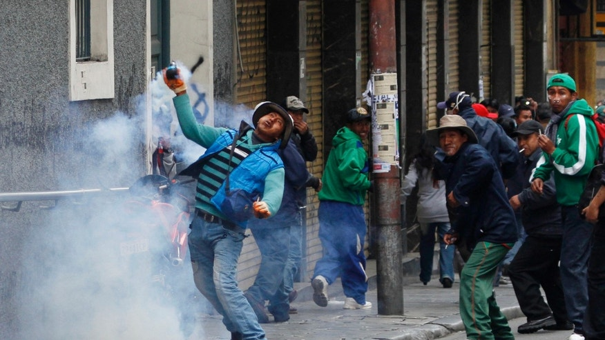 A demonstrator returns a tear gas canister fired by police during a protest by striking miners in La Paz, Bolivia, Thursday, May 16, 2013. Workers from the workers union Central Obrera Boliviana (COB) began an indefinite strike on May 6 to demand the government of President Evo Morales improve the pension law. (AP Photo/Juan Karita)