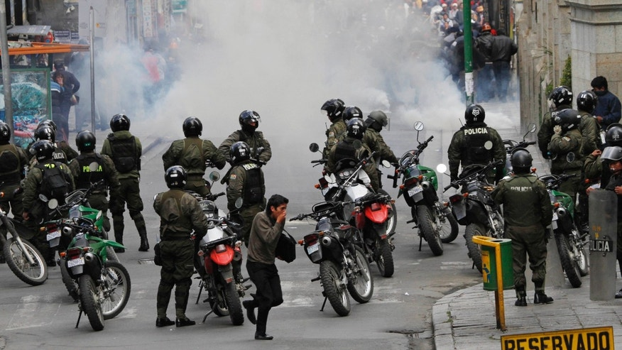 Police stand behind tear gas after firing it at striking miners after the miners' march ended in clashes in La Paz, Bolivia, Thursday, May 16, 2013. Workers from the workers' union Central Obrera Boliviana (COB) began an indefinite strike on May 6 to demand the government of President Evo Morales improve the pension law. (AP Photo/Juan Karita)