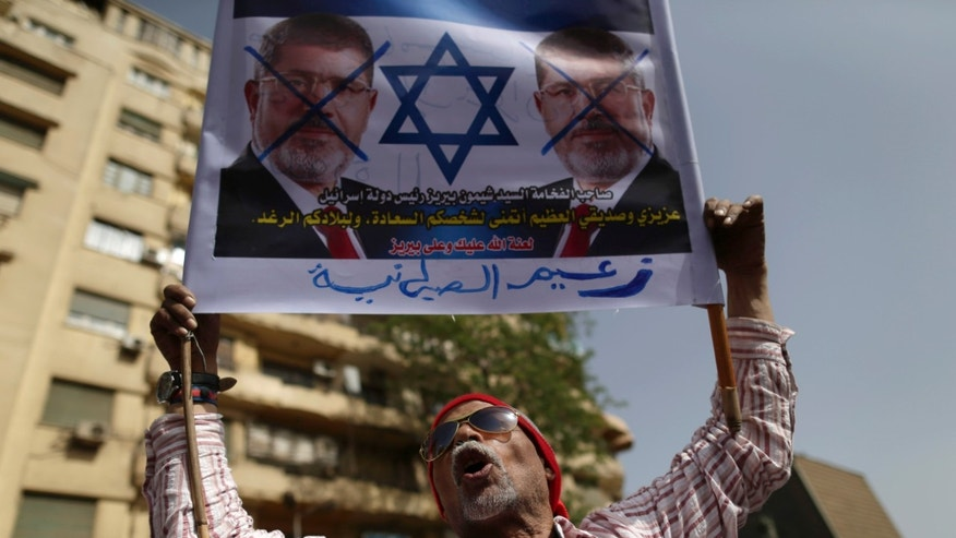 "An Egyptian protester shouts anti-President Mohammed Morsi slogans in Tahrir Square, in Cairo, Egypt, Friday, May 17, 2013. Hundreds of protesters gathered to demand early presidential elections and the removal of the Muslim Brotherhood's regime. Arabic on the poster reads, ""Mohammed Morsi, the leader of Zionism."" (AP Photo/Hassan Ammar)"
