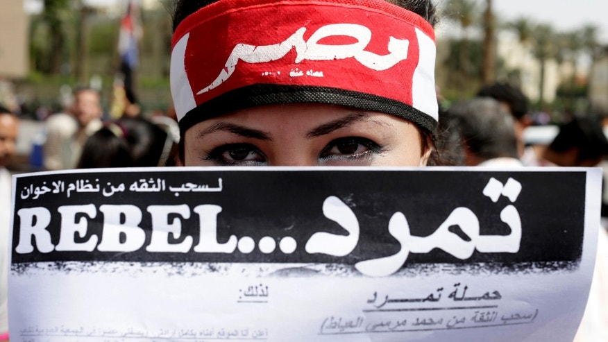 "An Egyptian activist covers her face with an applications for ""Tamarod"", Arabic for ""rebel"", a campaign calling for the ouster of Egyptian President Mohammed Morsi and for early presidential elections, during a protest in Tahrir Square, in Cairo, Egypt, Friday, May 17, 2013. Hundreds of protesters gathered to demand early presidential elections and the removal of the Muslim Brotherhood's regime. (AP Photo/Hassan Ammar)"