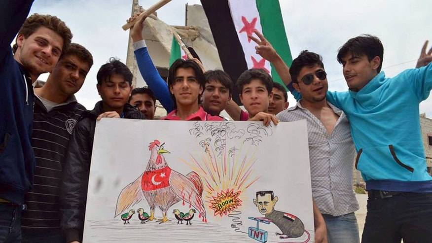This citizen journalism image provided by Edlib News Network, ENN, which has been authenticated based on its contents and other AP reporting, shows anti-Syrian regime protesters holding a placard with a caricature of Syrian President Bashar Assad during a demonstration in Kafr Nabil, in Idlib province, northern Syria, Friday, May 17, 2013. Rights activists have found torture devices and other evidence of abuse in government prisons in the first Syrian city to fall to the rebels, Human Rights Watch said in a report Friday. (AP Photo/Edlib News Network ENN)