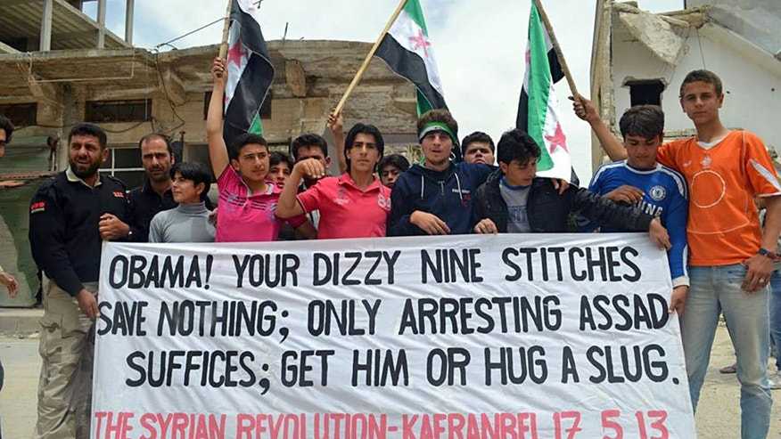 This citizen journalism image provided by Edlib News Network, ENN, which has been authenticated based on its contents and other AP reporting, shows anti-Syrian regime protesters carrying a banner during a demonstration in Kafr Nabil in Idlib province, northern Syria, Friday, May 17, 2013. Rights activists have found torture devices and other evidence of abuse in government prisons in the first Syrian city to fall to the rebels, Human Rights Watch said in a report Friday. (AP Photo/Edlib News Network ENN)