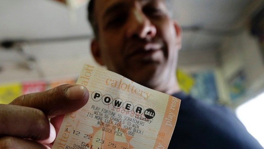 Joe Fajardo poses holding his Powerball lottery ticket after buying it at a store Saturday, May 18, 2013, in the Barrio Logan neighborhood of San Diego. With the majority of possible combinations of Powerball numbers in play, someone is almost sure to win the lottery game's highest jackpot on Saturday night, a windfall of hundreds of millions of dollars â and that's after taxes. (AP Photo/Gregory Bull)