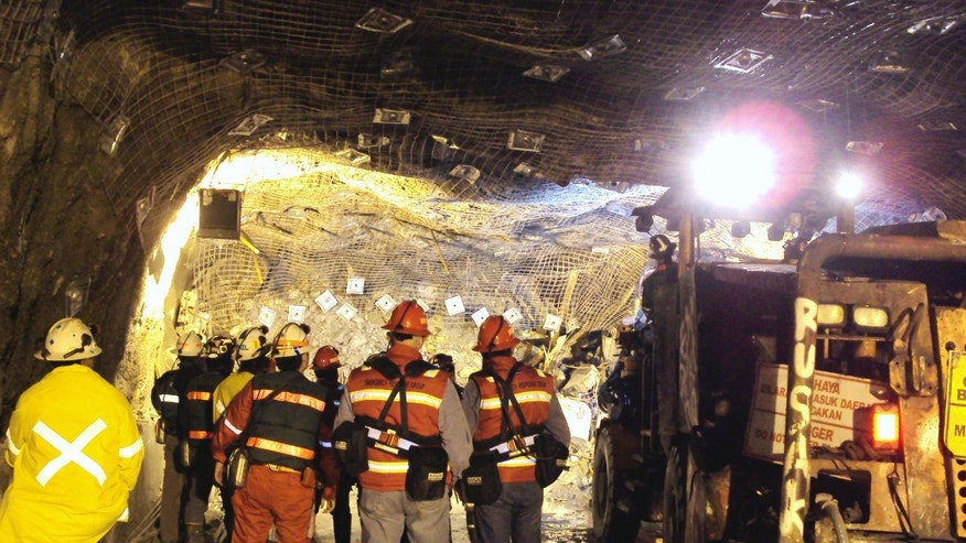 In this photo taken and released by PT Freeport Indonesia  Friday, May 17, 2013, the Indonesian unit of Arizona-based Freeport-McMoRan Copper & Gold Inc, rescuers gather inside a tunnel that collapsed on Tuesday morning as they continue their attempt to rescue trapped workers at Big Gossan mining area in Mimika, Papua province, Indonesia. Mining activities at a giant U.S.-owned gold and copper mine in Indonesia are halted for four consecutive days as rescuers manually dig through a caved-in mine tunnel looking for about 23 trapped workers, the mine operator said. (AP Photo/PT Freeport Indonesia) NO ARCHIVE, NO SALES