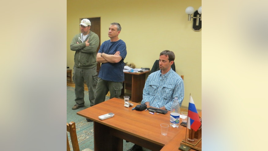 In this handout photo provided by the FSB, acronym for Russian Federal Security Service, a man claimed by FSB to be Ryan Fogle, right, a third secretary at the U.S. Embassy in Moscow, with Embassy officials at left, sits in the the FSB offices in Moscow, easrly Tuesday, May 14, 2013. Russia's security services say they have caught a U.S. diplomat who they claim is a CIA agent in a red-handed attempt to recruit a Russian agent. Ryan Fogle, a third secretary at the U.S. Embassy in Moscow, was carrying special technical equipment, disguises, written instructions and a large sum of money when he was detained overnight, the FSB said in a statement Tuesday. Fogle was handed over to U.S. embassy officials, the FSB,  said. (AP Photo/FSB Public Relations Center)