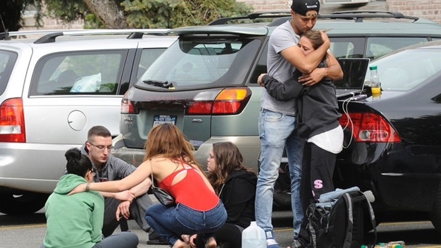 Hofstra University students gather near the house where another student and an armed intruder were killed during an overnight house break-in next to the campus, Friday, May 17, 2013, in Uniondale, N.Y. (AP Photo/ Louis Lanzano)