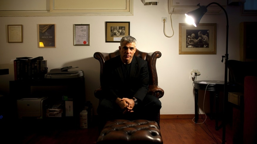 File - In this Jan.16, 2013 file photo, Yair Lapid, popular former TV anchorman and head of the new centrist party Yesh Atid, poses for a portrait at his house during an interview for the Associated Press, in Tel Aviv, Israel. Lapid, Prime Minister Benjamin Netanyahu's senior coalition partner, said in a published interview Sunday, May 19, 2013, that reaching a final peace agreement with the Palestinians is unrealistic at the current time and that the sides should instead pursue an interim arrangement. (AP Photo/Oded Balilty, File)