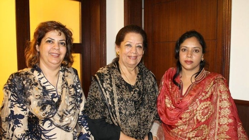 In this undated photo released by the Pakistan Tehreek-e-Insaf (PTI, Movement for Justice) party press office in Karachi, Zohra Shahid, center, a senior member of former Pakistani cricket star Imran Khan's Pakistan Tehreek-e-Insaf party in Sindh, poses with unidentified women at an unknown location in Pakistan. Police said gunmen on a motorcycle shot and killed Shahid outside her home on Saturday, May 18, 2013,  in the city of Karachi in southern Sindh province. (AP Photo/PTI)