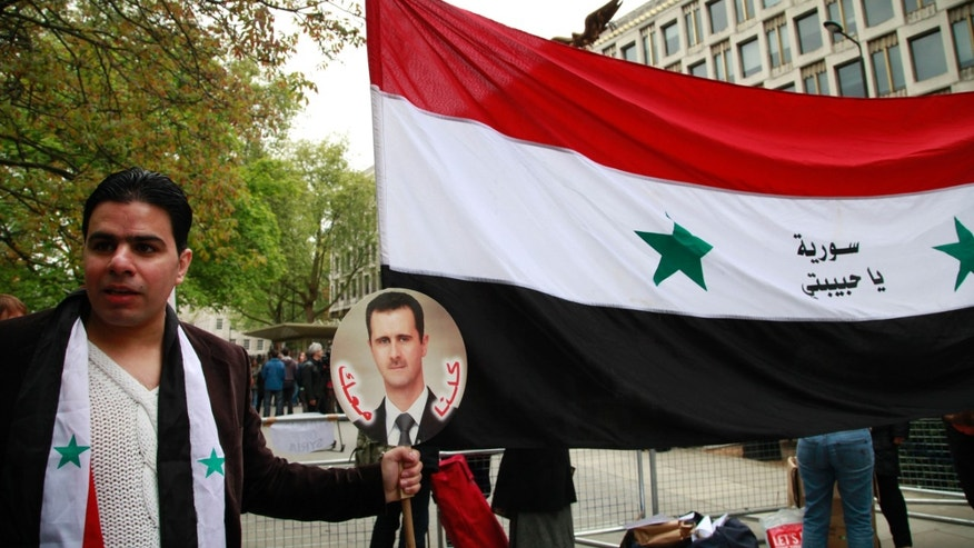 A Syrian supporting the regime of Syrian President Bashar Assad, holds a placard with his picture and the national flag as he participates in a protest outside the US Embassy in central London, Saturday, May 18, 2013. (AP Photo/Lefteris Pitarakis)