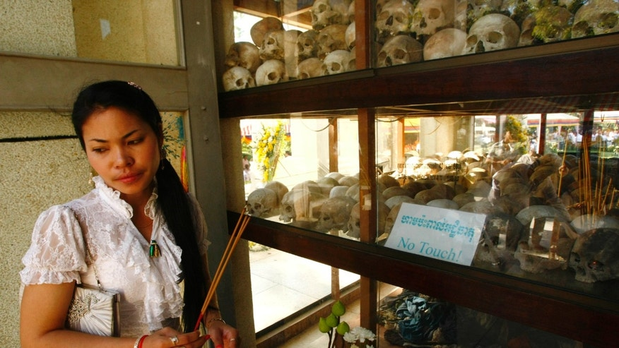 "A Cambodian woman stands with burning incense sticks as she visits a memorial holding skulls of the Khmer Rouge victims at Choeung Ek ""Killing Field"" in Phnom Penh, Cambodia, Monday, May 20, 2013. Cambodian Buddhist monks, nuns, civil servants, students attend the annual ""Day of Anger"" events to remember the atrocities and killings committed under the Khmer Rouge's 1975-79 rule. (AP Photo/Heng Sinith)"
