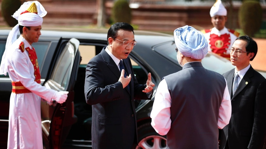 Chinese premier Li Keqiang, second left, talks to Indian Prime Minister Manmohan Singh, second right, upon Li's arrival for a ceremonial reception at the Presidential Palace in New Delhi, India, Monday, May 20, 2013. Just weeks after a tense border standoff, China's new premier visited India on Sunday on his first foreign three-day trip as the neighboring giants look to speed up efforts to settle a decades-old boundary dispute and boost economic ties. (AP Photo/Saurabh Das)