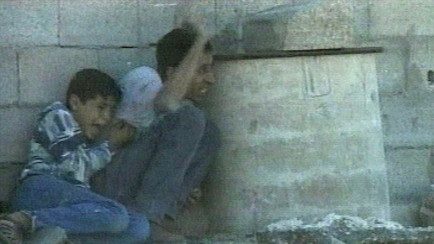 **  FILE  ** In this Sept. 30, 2000 file image from television, Jamal al-sutra signals his position while protecting his 12-year-old son Mohammed al-Dura, as they shelter behind a barrel from crossfire near Netzarim Jewish settlement in the southern Gaza Strip. More than a dozen years later, the death of a Palestinian boy allegedly shot by Israeli troops in Gaza continues to stir emotions on both sides of the conflict. A new Israeli report that tries to debunk the Palestinian narrative of the incident shows no signs of ending the saga, which for Palestinians has became a symbol of Israeli oppression and for Israel is a nasty smear campaign aimed at demonizing it. (AP Photo/France 2, Fille)  **  NO SALES TV OUT ***FRANCE OUT ***