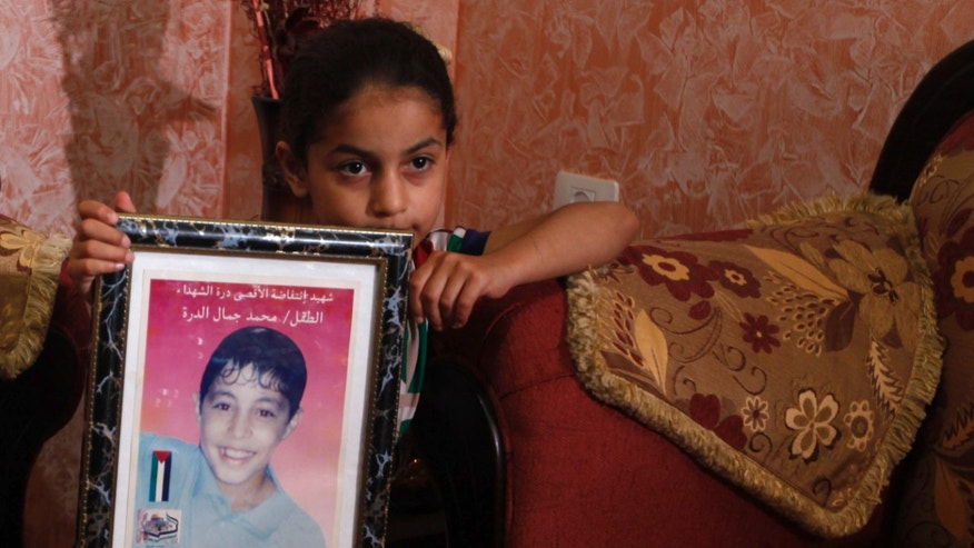 Baraa al-Dura, sister of Mohammed al-Dura poses with a picture of Mohammed at her home in Bureij Refugee Camp in the Gaza Strip, Monday, May 20, 2013. Mohammed al-Dura was killed during an exchange of gunfire between Israeli troops and Palestinian police on Gaza Strip on Sept. 30, 2000. More than a dozen years later, the death of a Palestinian boy allegedly shot by Israeli troops in Gaza continues to stir emotions on both sides of the conflict. A new Israeli report that tries to debunk the Palestinian narrative of the incident shows no signs of ending the saga, which for Palestinians has became a symbol of Israeli oppression and for Israel is a nasty smear campaign aimed at demonizing it. (AP Photo/Hatem Moussa)