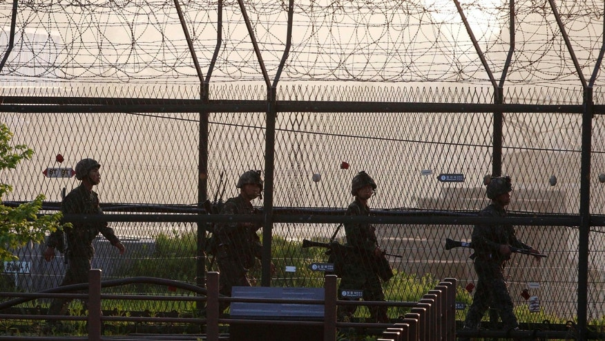 May 20, 2013 - South Korean Army soldiers patrol along a barbed-wire fence near the border village of the Panmunjom in Paju, South Korea.