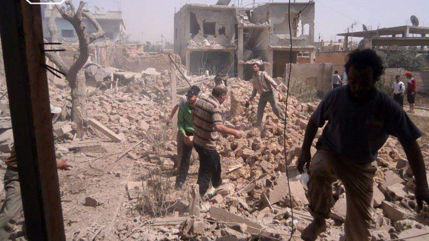 In this Saturday, May 18, 2013 citizen journalism image provided by Qusair Lens which has been authenticated based on its contents and other AP reporting, shows Syrians inspecting the rubble of damaged buildings due to government airstrikes, in Qusair, Homs province, Syria. The town of Qusair has been besieged for weeks by regime troops and pro-government gunmen backed by the Lebanese militant Hezbollah group. The siege is part of a withering offensives forces loyal to Syrian President Bashar Assad have been pushing in recent weeks to regain control of the towns and villages along the Lebanese frontier. (AP Photo/Qusair Lens)