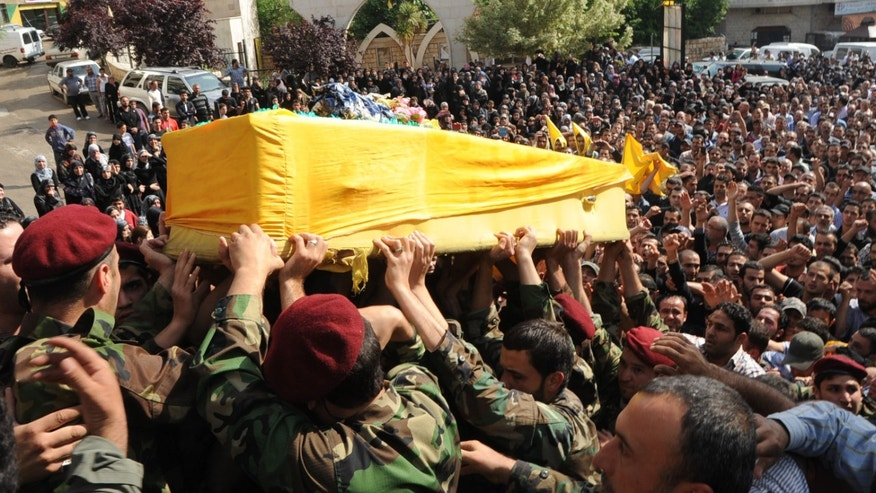 Hezbollah fighters in their military uniform, foreground, carry the coffin of Hezbollah fighter Hassan Faisal Shuker, 18, who was killed in a battle against Syrian rebels in the Syrian town of Qusair, during his funeral procession in his hometown of Nabi Sheet in the eastern Bekaa valley, Lebanon, Monday May 20, 2013. Fierce street fighting in Qusair, Syria, near the Lebanese border has killed at least 28 elite members of Lebanon's militant Hezbollah group, activists said Monday, as Syrian government forces pushed deeper into the strategic, opposition-held town. The barefaced Hezbollah involvement -- several funerals for group members were held in Lebanon Monday -- edges the war further into a regional sectarian conflict pitting the Middle East's Iranian-backed Shiite axis against Sunnis. (AP Photo)