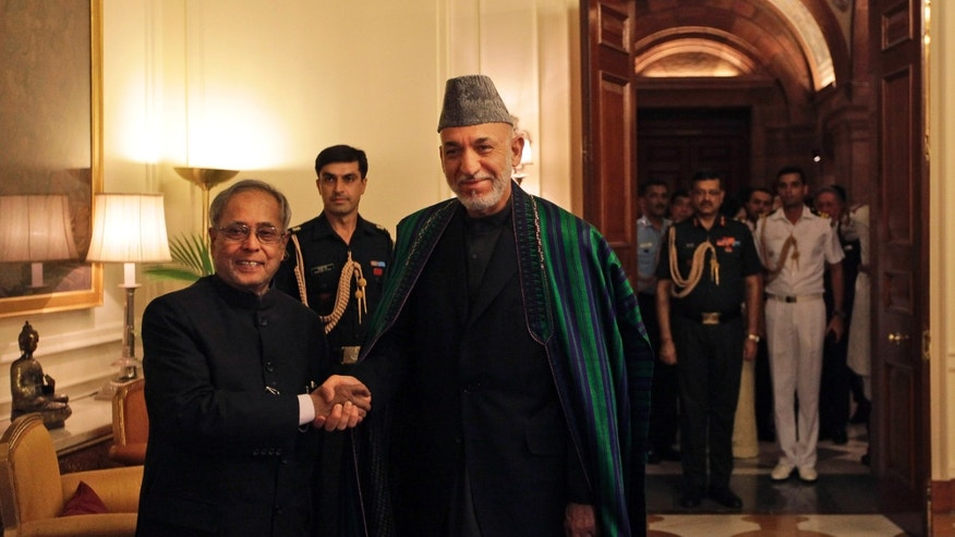 Indian President Pranab Mukherjee, left, and Afghan President Hamid Karzai pose for photographers at the Indian Presidential Palace in New Delhi, India, Tuesday, May 21, 2013. Karzai is meeting with Indian leaders and is expected to seek increased military aid from India. India has invested more than $2 billion in Afghan infrastructure, including highways and hospitals and rural electricity projects. India is helping the Afghan government rebuild its police forces, judiciary and diplomatic services. (AP Photo/Manish Swarup)