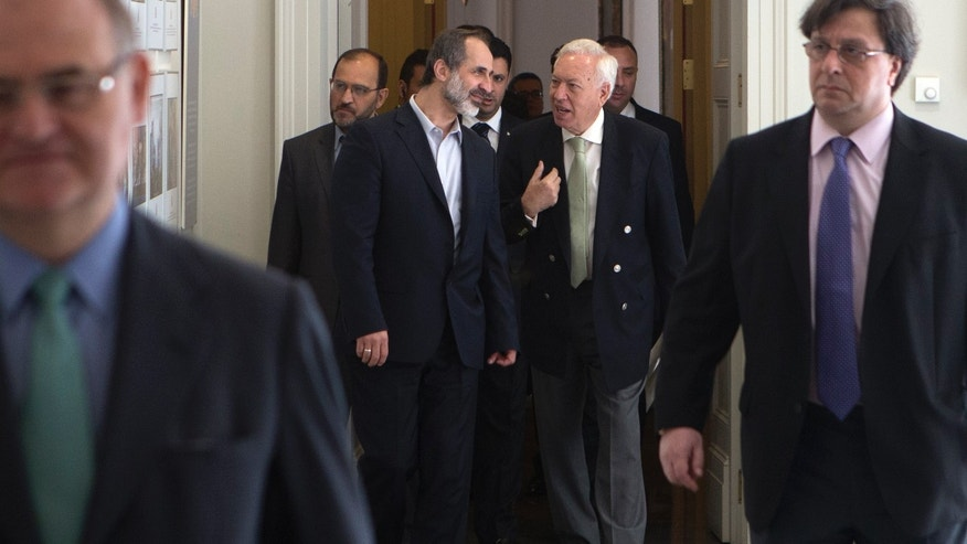 Mouaz al-Khatib, former chief of the Syrian National Coalition, rear left, walks with Spain's Foreign Minister Jose Manuel Garcia-Margallo, rear right, on their way to give a joint news conference at the foreign ministry in Madrid, Spain, Tuesday May 21, 2013. Syrian opposition groups meeting in Spain say they oppose all negotiation with President Bashar Assad's government unless it is aimed at his giving up of power. Some 80 opposition representatives from inside and outside the country concluded a two-day meeting Tuesday, saying Assad would neither form part of any transition government nor have any role in Syria's future. (AP Photo/Paul White)