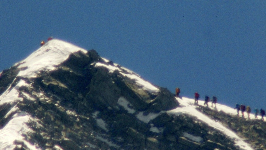 A team of climbers, right, led by 80-year-old Japanese mountaineer Yuichiro Miura approach the summit of Mount Everest on Thursday, May 23, 2013. Miura on Thursday became the oldest man to reach the top of Mount Everest, a Nepali official and Miura's Tokyo-based support team said. The photo was taken with a telephoto lens from an altitude of 5,550 meters (18,208 feet). It is not clear which of the climbers in the photo is Miura. (AP Photo/Kyodo News) JAPAN OUT, MANDATORY CREDIT