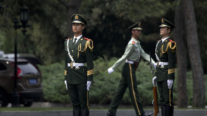 Chinese paramilitary police officers stand in position at the gate of the Diaoyutai State Guesthouse, where a car believed to be carrying North Korea's Vice Marshal Choe Ryong Hae, a senior Workers' Party official and the military's top political officer, arrives in Beijing Thursday, May 23, 2013. After months of ignoring Chinese warnings to give up nuclear weapons, North Korean leader Kim Jong Un sent the high-level confidant to Beijing on Wednesday, in a possible effort to mend strained ties with his country's most important ally and a sign that he may be giving diplomacy a chance. (AP Photo/Andy Wong)