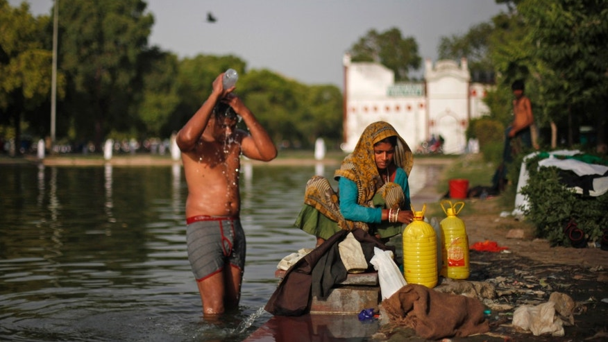 An Indian man bathes as a woman prepares to wash clothes at a lake on a hot afternoon in New Delhi, India, Wednesday, May 22, 2013. The capital city has been reeling under a heat wave with temperature crossing 44 degree Celsius (112 Fahrenheit) on Wednesday. (AP Photo/Altaf Qadri)