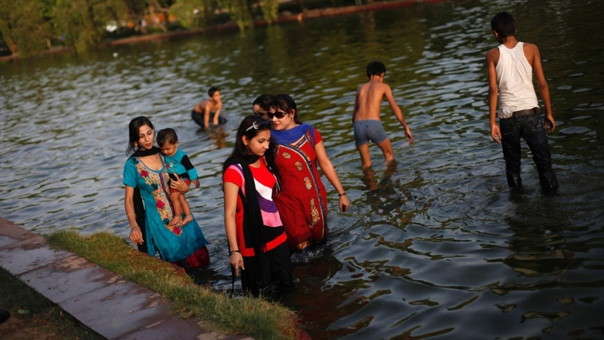 Indian women wade in a lake on a hot afternoon in New Delhi, India, Wednesday, May 22, 2013. The capital city has been reeling under a heat wave with temperature crossing 44 degrees Celsius (112 Fahrenheit) on Wednesday. (AP Photo/Altaf Qadri)