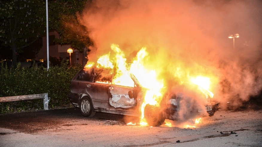 FILE - In this May 21, 2013 file photo, a burnt out car,  in the Stockholm suburb of Kista after youths rioted in several different suburbs around Stockholm for a third executive night. Immigrant youth in sleepy suburban communities run amok, hurling rocks at police and torching cars, restaurants and culture centers. It isn't France or Britain, but Sweden _ a Scandinavian bastion of generous social welfare and egalitarian political culture. Though this week's rioting outside Stockholm was triggered by perceived police brutality, observers say that there has been a surge of angst in society as inequality rises on a backdrop of burgeoning immigrant numbers.  (AP Photo/Scanipx Sweden, Fredrik Sandberg, File)  SWEDEN OUT
