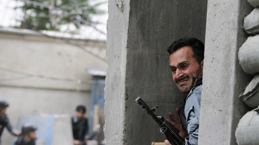 May 24, 2013 - An Afghan policeman takes cover following a suicide attack in Kabul, Afghanistan.