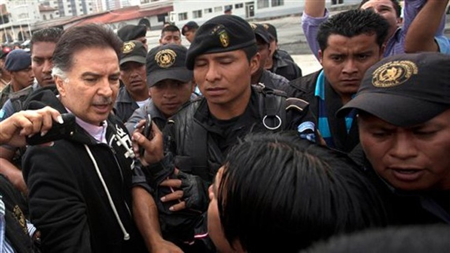 Former president of Guatemala, Alfonso Portillo, left, speaks to the press as he is led by police to an aircraft that will fly him to the United States Friday, May 24, 2013.