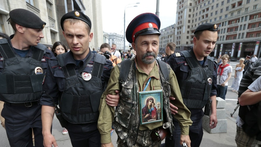 "Police detain an anti-gay protester wearing a Cossack hat and an Orthodox Christian icon during an unsanctioned gay rally in downtown Moscow, Saturday, May 25, 2013. The Kremlin initiated a bill banning ""propaganda of homosexuality"" and routinely banned gay rallies and parade.  (AP Photo/Ivan Sekretarev)"