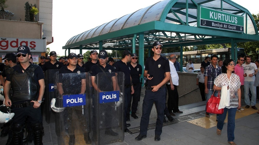 """Riot police stand at the entrance in anticipation of young Turkish couples expected to kiss in protest against subway official's harassment of a couple for kissing in public last week, at a subway stop in Ankara, Turkey, Saturday, May 25, 2013.  Last week, Ankara subway officials made a reproaching announcement asking passengers """"to act in accordance with moral rules,"""" after spotting the couple kissing through security cameras.(AP Photo/Burhan Ozbilici)"""