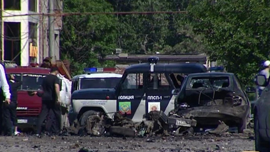 This image taken from AP video shows the scene of a blast with wreckage of a police car and debris littered over the ground in Makhachkala in the southern Russian region of Dagestan on Saturday, May 25, 2013. A female suicide bomber blew herself up in the southern Russian region of Dagestan on Saturday, injuring at least 18, including two children and five police officers, authorities said. The attacker was later identified as a widow of two Islamic radicals killed by security forces. It was the first suicide bombing in Dagestan since the Boston Marathon attacks last month. (AP Photo/AP video)