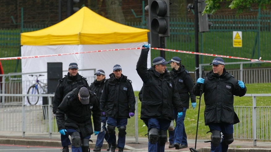 Police search team leave the scene of a terror attack in Woolwich, southeast London, Thursday, May 23, 2013. A member of armed forces was attacked and killed by two men on Wednesday. (AP Photo/Sang Tan)