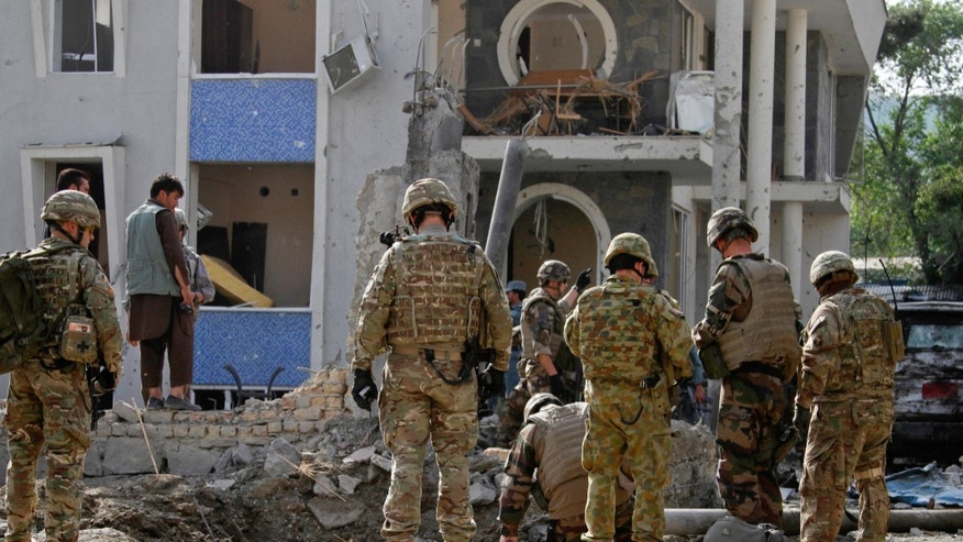 Foreign troops, part of the NATO-led International Security Assistance Force (ISAF), investigate the site a day after an assault on an international compound in Kabul, Afghanistan, May 25, 2013. A would-be suicide bomber died when his explosives-rigged vest went off prematurely in Afghanistan's capital on Saturday morning, police said. The apparent failed attack came a day after a major Taliban assault on an international compound in Kabul left many people dead including, the attackers.(AP Photo/Ahmad Jamshid)