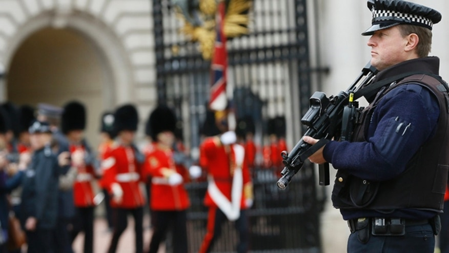 May 23, 2013: An armed police officer keeps guard as British soldiers march out of Buckingham Palace after the changing of the guard ceremony in London.