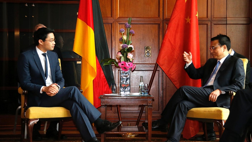 German Economy Minister Philipp Roesler, left, listens to  Chinese Premier Li Keqiang during a meeting in Berlin Monday  May 27, 2013. (AP Photo/Tobias Schwarz,Pool)