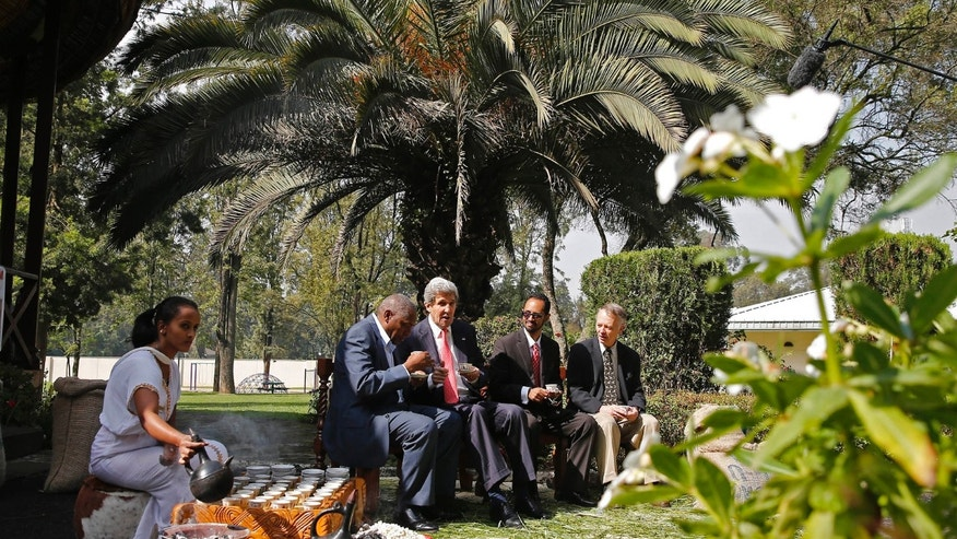 U.S. Secretary of State John Kerry, third from right, enjoys a coffee ceremony is performed by Getenesh Abush, left, during his visit to Addis Ababa, Ethiopia, Sunday May 26, 2013. Kerry visited Ethiopia to mark the 50th anniversary of the African Union. The other men in the photo are unidentified. (AP Photo/Pool, Jim Young)