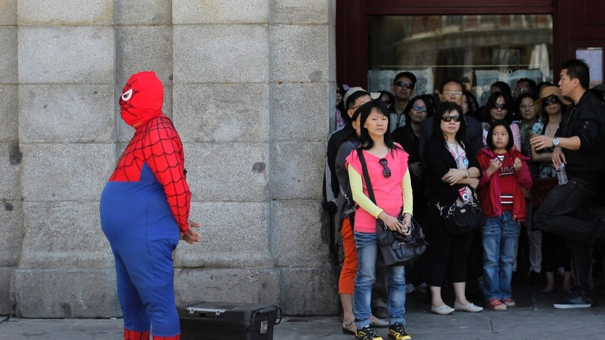 A man wearing a spiderman outfit performs for money as tourists look at the main square in Madrid, Spain, Thursday, May 23, 2013. Financial markets around the world were roiled Thursday after Japanese stocks suffered their biggest reverse since the tsunami that hit the country over two years ago. Spain has had to pay higher interest rates on selling euros 4 billion euros ($5.2 billion) in a bond auction that coincided with a sharp drop in global financial markets on worries over China's economy. Spain's Ibex 35 stock index was down 2 percent. (AP Photo/Andres Kudacki)