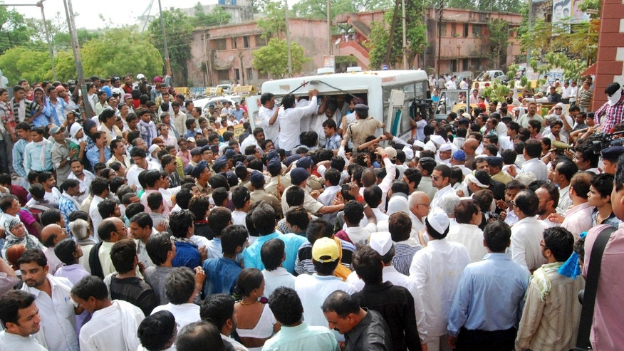 People gather outside the Congress party office as bodies of party leaders killed in Saturday's Maoist attack are taken away for cremation in Raipur, Chhattisgarh state, India, Sunday, May 26, 2013. Officials reacted with outrage Sunday to an audacious attack by about 200 suspected Maoist rebels who set off a roadside bomb and opened fire on a convoy carrying Indian ruling Congress party leaders and members in an eastern state, killing at least 24 people and wounding 37 others. (AP Photo)