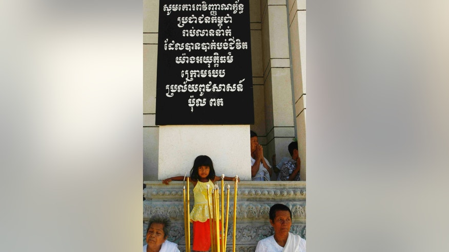 "In this photo taken, May 20, 2013, a Cambodian girl, center, stands under an inscription board which reads ""Would you please kindly show your respect to many million people who were killed under the genocidal Pol. Pot regime"" as it hangs on a wall of a memorial housing skulls of the Khmer Rouge victims at Choeung Ek ""Killing Field"" in Phnom Penh, Cambodia. Cambodian Prime Minister Hun Sen appealed Monday to member of parliaments urgently drafting a law in aims to punishment an opposition party leader from he recently comments that former Khmer Rouge's notorious S-21 prison was not real but created by Vietnamese, a move that could bar his opponent from participant upcoming election. (AP Photo/Heng Sinith)"