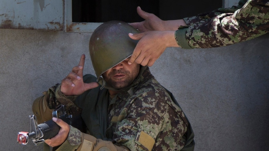 A military instructor adjusts the helmet of an Afghan Army soldier during a house-to-house search at a training facility in the outskirts of Kabul, Afghanistan on Wednesday, May 8, 2013. In roughly 90 percent of the country, Afghan police and soldiers are taking the fight to the Taliban alone, a first in 12 years of war. U.S. and NATO soldiers have slipped quietly into the background, taking on the role of advisor and providing backup when needed.  (AP Photo/Anja Niedringhaus)