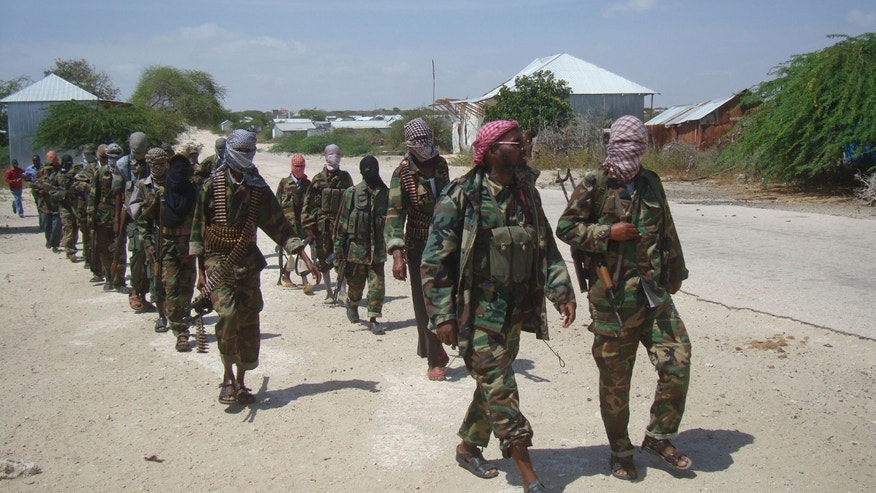 FILE - Members of Somalia's al- Shabab militant group patrol on foot on the outskirts of Mogadishu in this  Monday, March, 5, 2012 file photo. The slaying of a British soldier in east London cast a spotlight on radical preachers that influenced Michael Adebolajo, the attacker seen in videos with bloody hands wielding a butcher knife. It also raised questions about the reach of the terrorist group al-Shabab, after a British government official said one of the two men tried to go to Somalia to train or fight with the group.   (AP Photo, File)