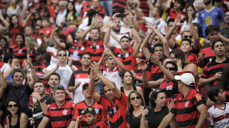 In this May 26, 2013 photo, fans cheer before the inaugural soccer match between Santos and Flamengo at the Mane Garrincha national stadium in Brasilia, Brazil. The ``Beautiful Game'' has become the ``Pricey Game.'' This year's Confederations Cup and next year's World Cup, are speeding the changes. The national game is getting a different look with the use of numbered seating, a transformation that's been going on for several years.  For decades, Brazilians simply raced into the stadiums and grabbed the best spots, some sitting, others standing. (AP Photo/Eraldo Peres)