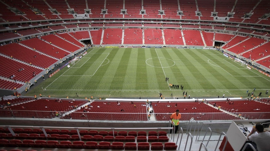 In this May 26, 2013 photo, the field sits empty inside the Mane Garrincha national stadium before the inaugural soccer match between Santos and Flamengo in Brasilia, Brazil. For decades, Brazilians simply raced into the stadiums and grabbed the best spots, some sitting, others standing in a crush amid thousands of others. Traditional general admission is being eliminated with luxury boxes and modern seating taking over at the six stadiums being used for the Confederations Cup, and the additional six that are to be ready for the World Cup. (AP Photo/Eraldo Peres)