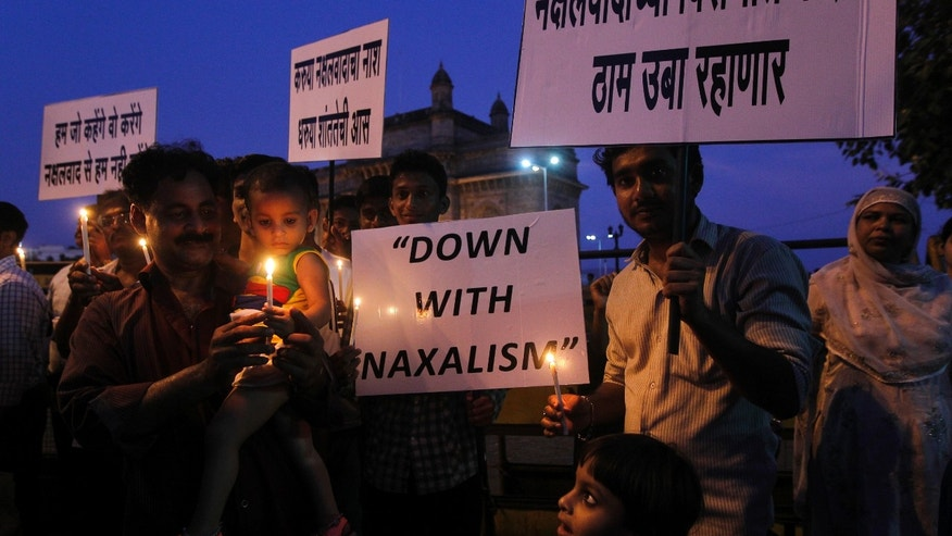 """India's Congress party workers hold placards during a candle light vigil for those killed in Saturday's Maoist attacks in Chhattisgarh state as they stand near the Gateway of India monument in Mumbai, India, Monday, May 27, 2013.Troops fanned out across central India on Monday in a massive manhunt days after hundreds of Maoist rebels attacked a convoy of ruling party members and leaders, killing 24 people in an area considered the stronghold of the rebels, police said. Placard in Marathi, right, reads, """"Congress stands strongly against Naxalism"""".(AP Photo/Rajanish Kakade)"""