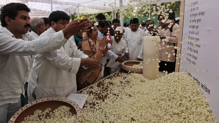 India's Congress party workers pay floral tribute to those killed in Saturday's Maoist attack in Chhattisgarh at a prayer meeting held at the party's headquarters in New Delhi, India, Monday, May 27, 2013. Troops fanned out across central India on Monday in a massive manhunt days after hundreds of Maoist rebels attacked a convoy of ruling party members and leaders, killing 24 people in an area considered the stronghold of the rebels, police said. (AP Photo/Manish Swarup)