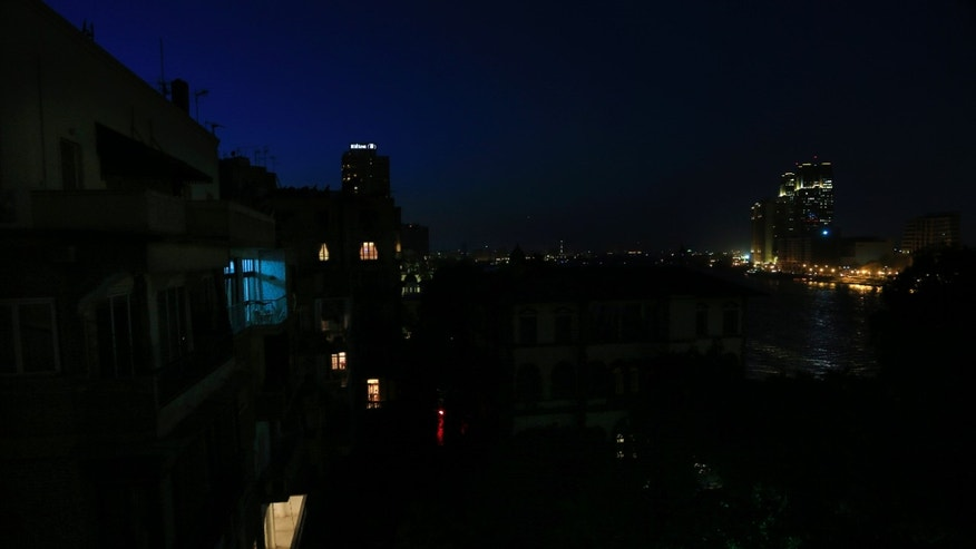 The Zamalek neighborhood of Cairo, during a power short cut, in Egypt, Sunday, May 26, 2013. In recent months, as temperatures rose, power cuts have become part of Egyptian daily routine, even in the most upscale districts of the capital. Along with a stuttering economy, traffic-clogging street protests, and a crime wave, they have come to symbolize the disorder of the post-Mubarak era. The government has urged citizens to cut down use of electricity during the summer and said it is working on securing enough funds to buy fuel to solve the problem. (AP Photo/Hassan Ammar)