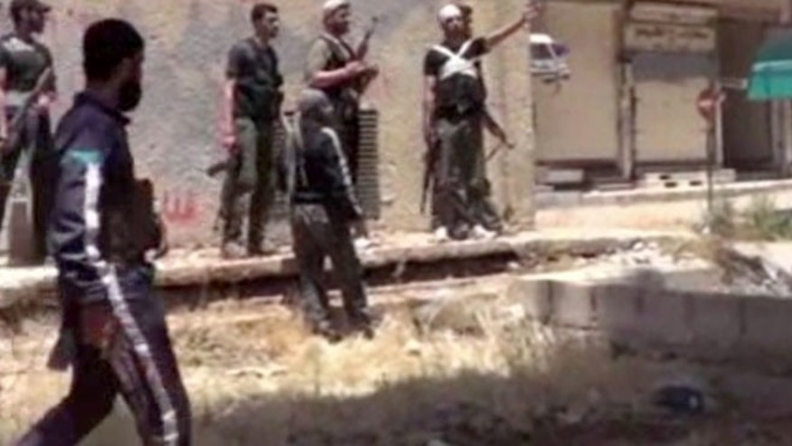 May 28, 2013: This image from amateur video obtained by a group which calls itself Ugarit News, which is consistent with AP reporting, shows rebel fighters in Daraa, Syria. Europe's decision to allow member states to arm Syrian rebels and Russia's renewed pledge to send advanced missiles to the Syria regime could spur an arms race in an already brutal civil war and increasingly turn it into a East-West proxy fight.