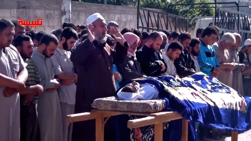 "In this image taken from video obtained from the Shaam News Network, which has been authenticated based on its contents and other AP reporting, Syrians participate in the  funeral prayer for Youssef Ghazi al-Sarmani who was killed in fighting between rebel and government forces, Monday, May 27, 2013. Logo in red reads, ""Talbiseh"". (AP Photo/Shaam News Network via AP video)"